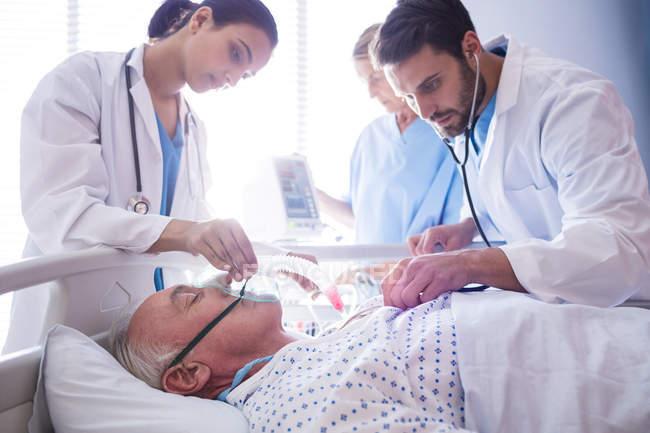 Equipo de médicos poniendo la máscara de oxígeno sobre la piel masculina senior paciente en el hospital - foto de stock