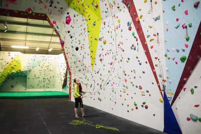 Formateur en tenant la corde près de mur d'escalade artificiel en gym — Photo de stock