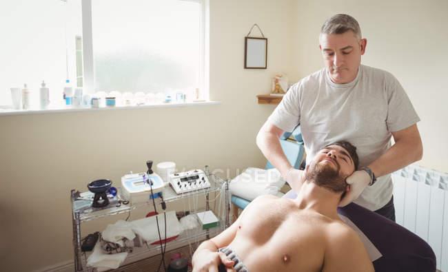 Fisioterapista che esamina il collo del paziente di sesso maschile in clinica — Foto stock