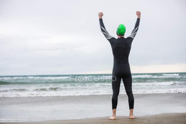 Rückansicht des glücklichen Athleten stehen am Strand mit seinen Händen angehoben — Stockfoto