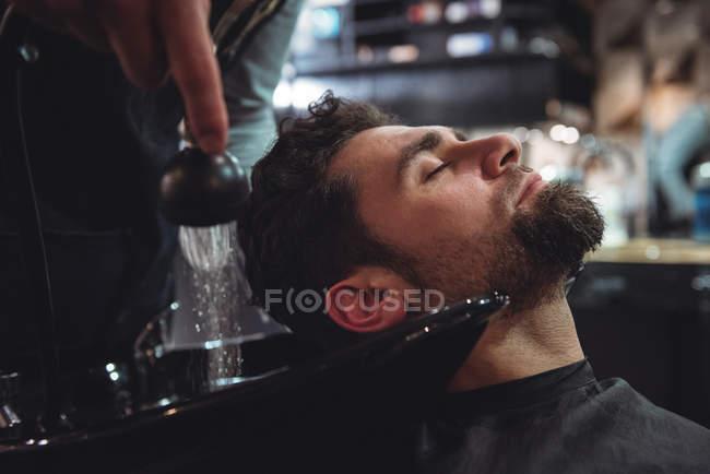 Uomo rilassante mentre si lava i capelli nel negozio di barbiere — Foto stock