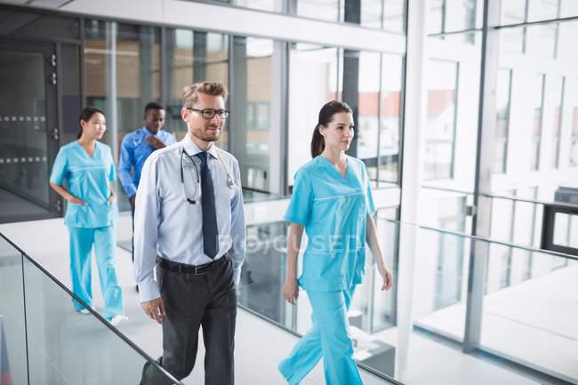 Врачи и медсестра идут по коридору в больнице — стоковое фото