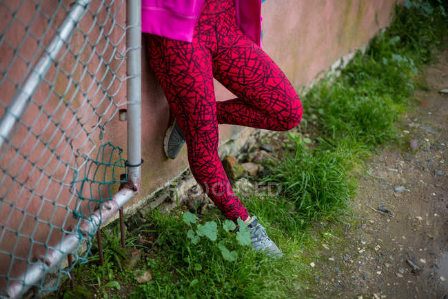 Low section of parkour woman standing against a wall — Stock Photo