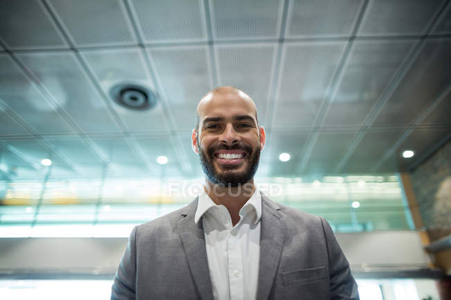 Portrait of smiling businessman standing in waiting area at airport terminal — Stock Photo