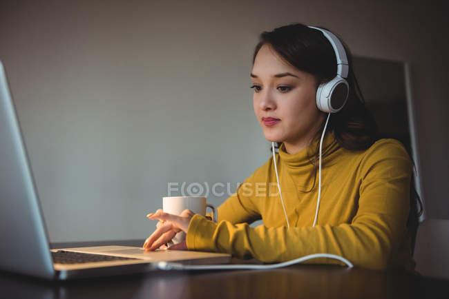 Frau hört Kopfhörer, während sie zu Hause im Arbeitszimmer Laptop benutzt — Stockfoto