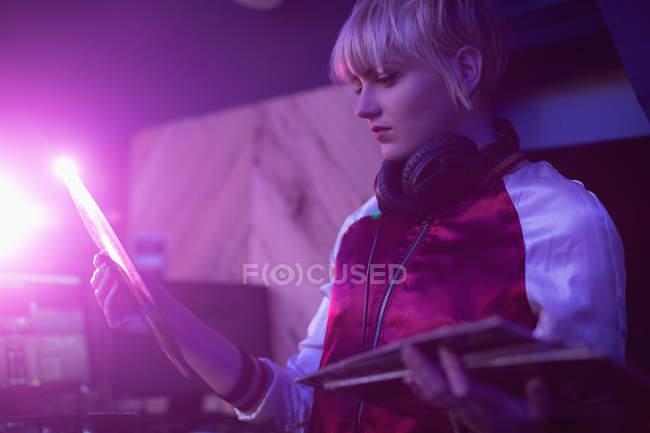 Beautiful female dj holding a vinyl disc record in bar — Stock Photo