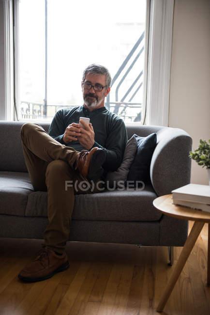Человек, использующий мобильный телефон в гостиной дома — стоковое фото
