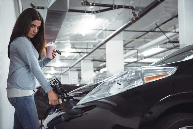 Belle femme recharge voiture électrique à la station de charge de véhicule électrique — Photo de stock