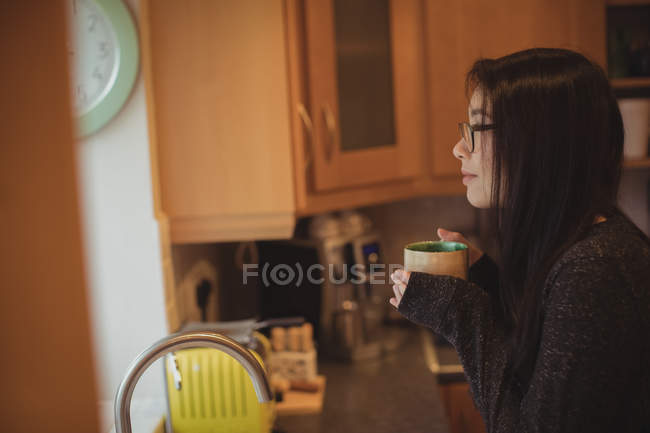 Thoughtful woman having coffee in kitchen at home — Stock Photo