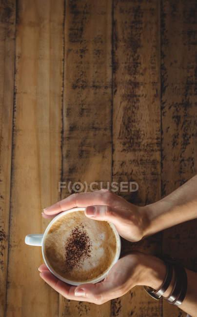 Primer plano de la mujer sosteniendo la taza de café en la cafetería - foto de stock