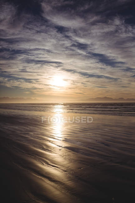Tranquil view of beach with cloudy sky at dusk — Stock Photo