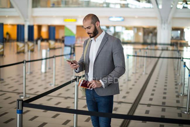 Empresario sosteniendo una tarjeta de embarque y comprobar su teléfono móvil en la terminal del aeropuerto - foto de stock