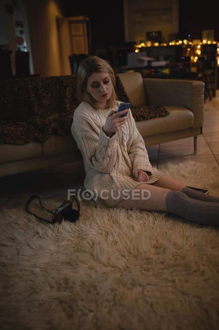 Frau mit Handy zu Hause sitzend — Stockfoto