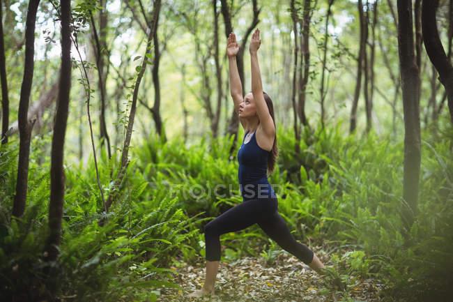Mujer realizando yoga en el bosque en un día soleado - foto de stock