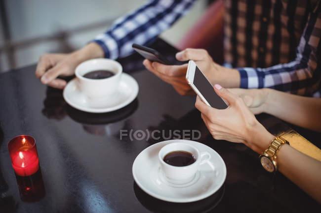 Casal com telefones móveis no restaurante — Fotografia de Stock