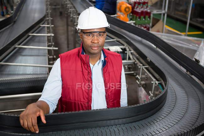 Портрет мужчины работника, стоя на конвейер завода — стоковое фото