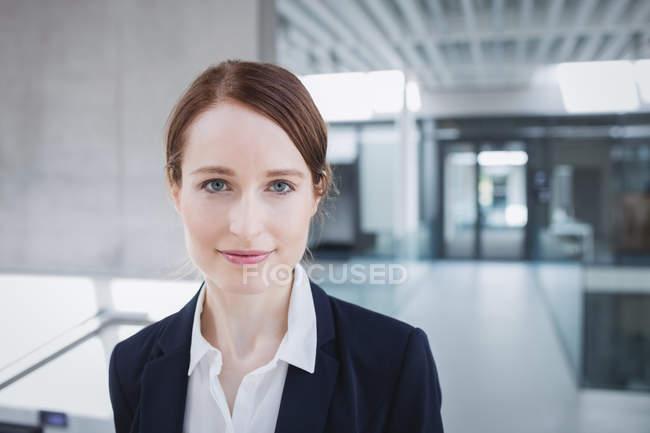 Portrait d'une femme d'affaires confiant, souriant à l'intérieur de bureau — Photo de stock