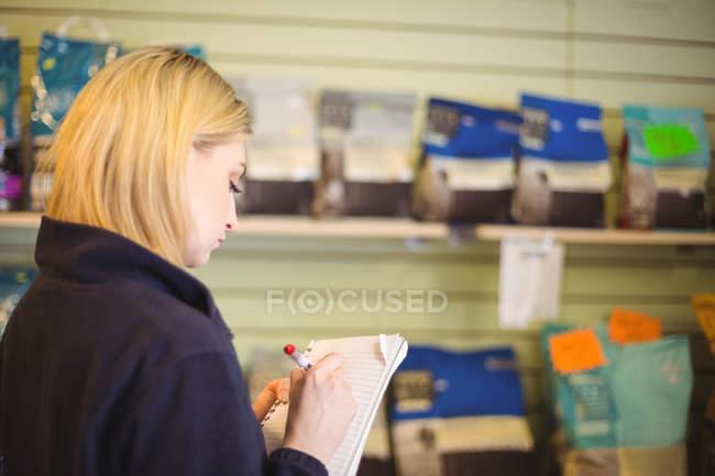Жінка писати блокнот у цеху собака догляд центр — стокове фото