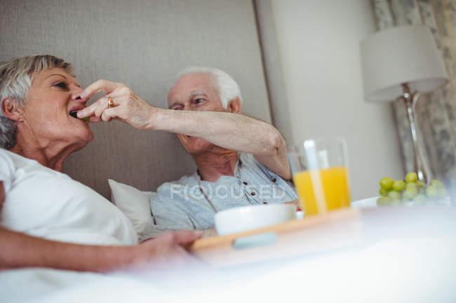 Couple aîné prenant le petit déjeuner sur le lit dans la chambre — Photo de stock