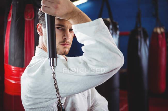 Портрет игрока в карате, практикующего с нунчаком в фитнес-студии — стоковое фото