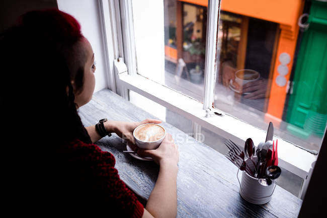 Thoughtful woman having coffee in cafe — Stock Photo