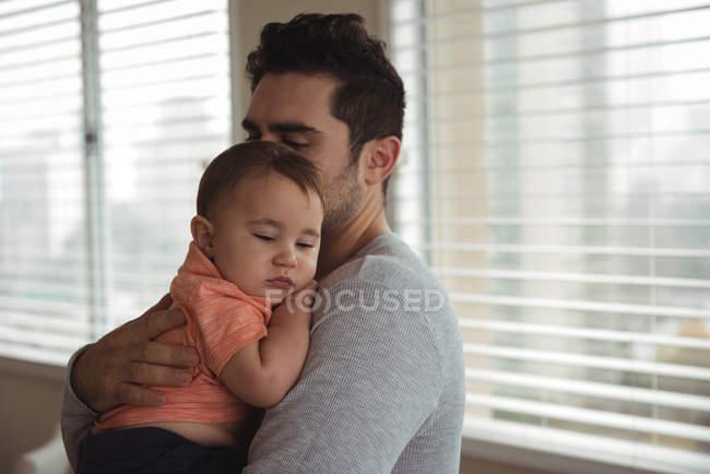 Середині дорослої людини втішний дитину сина в домашніх умовах — стокове фото