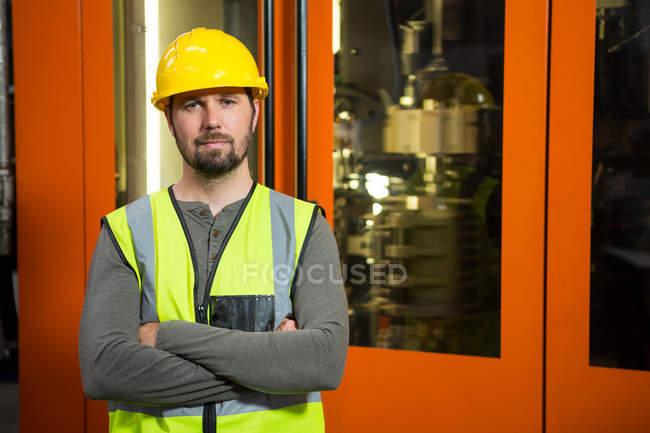 Porträt eines selbstbewussten männlichen Arbeiters, der in der Fabrik gegen Tür steht — Stockfoto