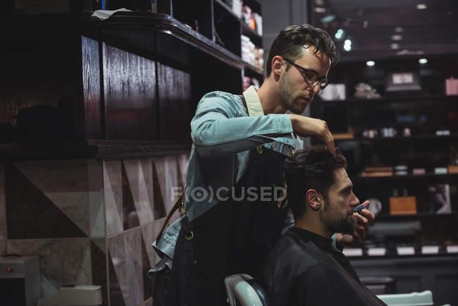 Parrucchiere styling cliente capelli in negozio di barbiere — Foto stock