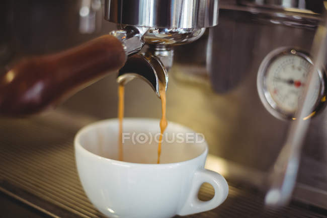 Close-up of espresso pouring from coffee machine in cafe — Stock Photo