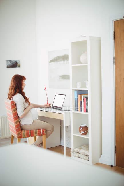 Беременная женщина с ноутбуком в кабинете дома — стоковое фото
