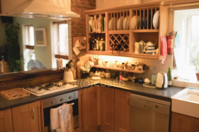 Vacío cocina en casa con platos en gabinete y aparatos - foto de stock