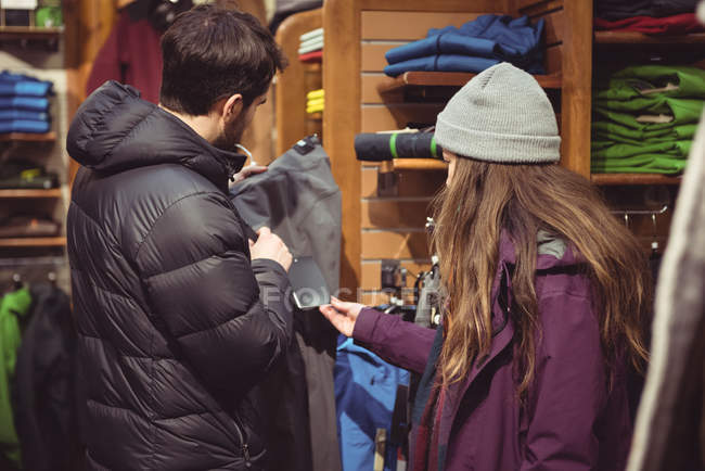 Couple selecting apparel together in a clothes shop — Stock Photo