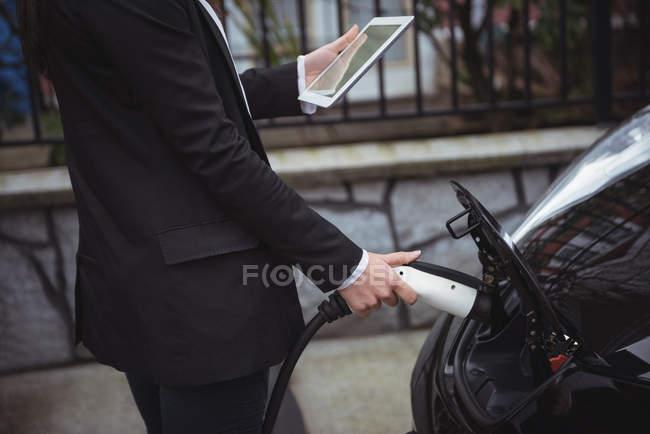 Section médiane de la femme à l'aide de tablette numérique tout en chargeant la voiture électrique à charge conductive pour véhicules — Photo de stock