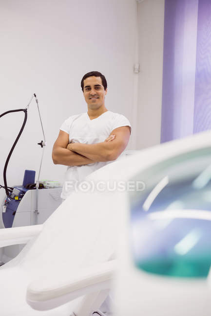 Portrait of smiling doctor standing with arms crossed at clinic — Stock Photo