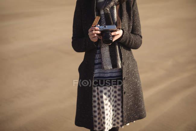 Frau mit Blick auf Fotos auf digitalen Kamera am Strand tagsüber — Stockfoto