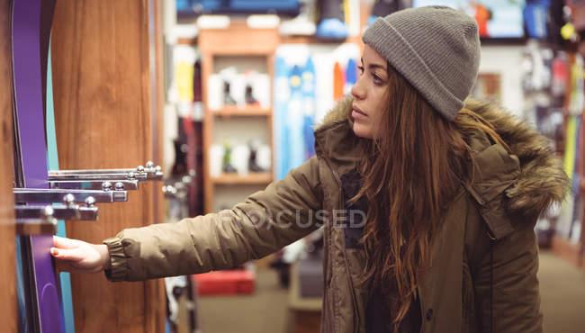 Bella donna che seleziona sci in un negozio — Foto stock