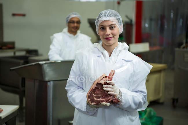 Портрет жіноче м'ясника, проведення м'яса на заводі м'яса — стокове фото