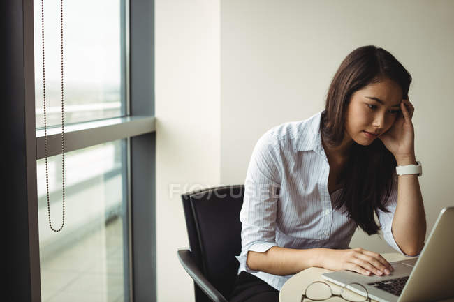 Бизнесвумен, работающая над ноутбуком в офисе — стоковое фото