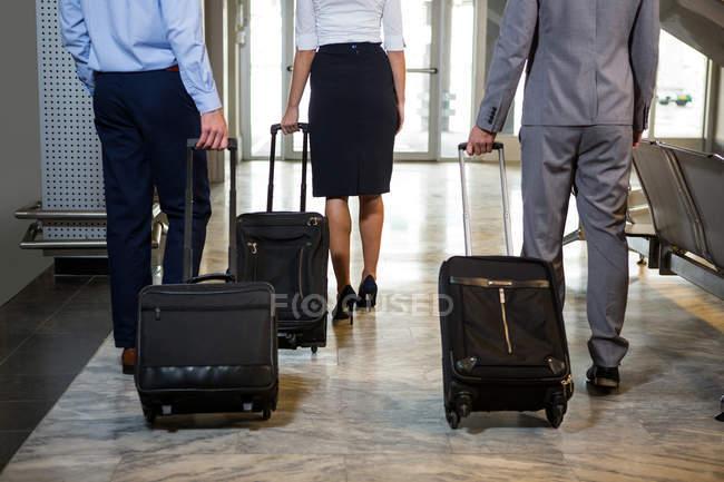 Geschäftsleute und Mitarbeiterinnen gehen mit Gepäck im Wartebereich am Flughafen — Stockfoto