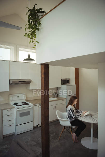 Woman using digital tablet in kitchen at home — Stock Photo