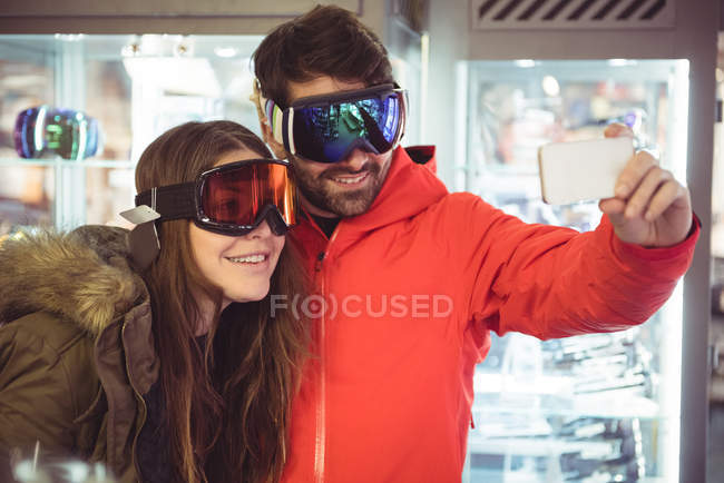 Couple in ski goggles taking a selfie using mobile phone — Stock Photo