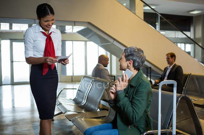 Línea aérea llegadas asistente control de pasaporte en la entrada área de espera en el aeropuerto - foto de stock