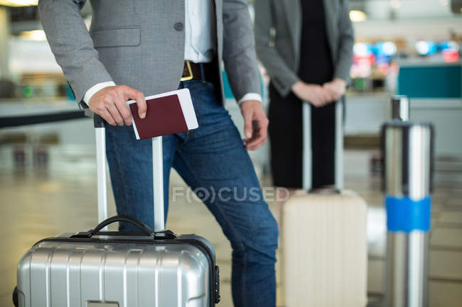 Business people waiting in queue at a check-in counter with luggage in airport terminal — Stock Photo