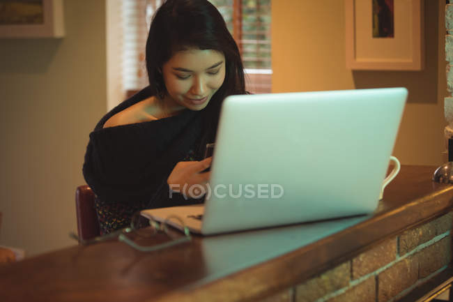Жінка за допомогою мобільних телефонів і ноутбуків на кухонного столу на дому — стокове фото