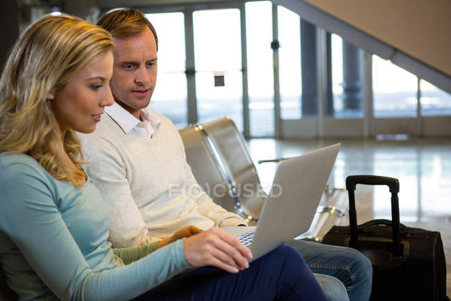 Couple sitting with laptop in the waiting area at airport terminal — Stock Photo