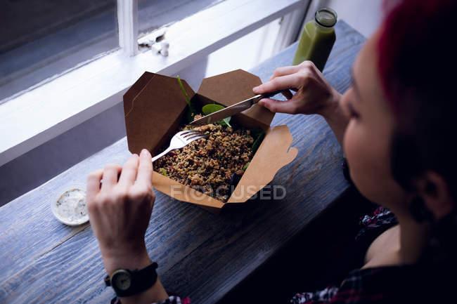 Bella donna che ha un'insalata da scatola in caffè — Foto stock
