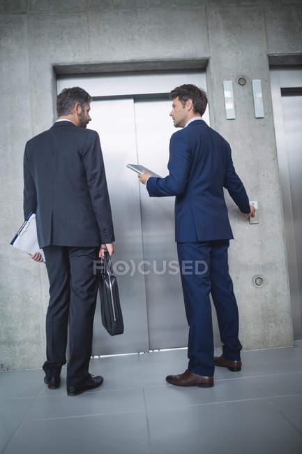 Hommes d'affaires permanent par l'ascenseur et appuyez sur la touche au bureau — Photo de stock
