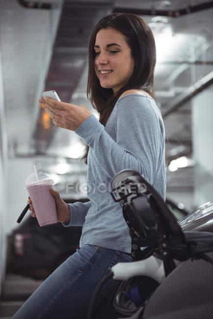 Femme souriante debout à côté d'une voiture et utilisant un téléphone portable à la borne de recharge du véhicule électrique — Photo de stock