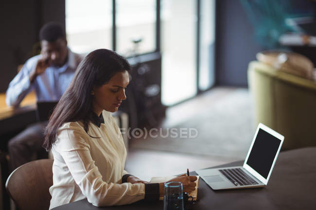 Businesswoman working at her desk in office — Stock Photo