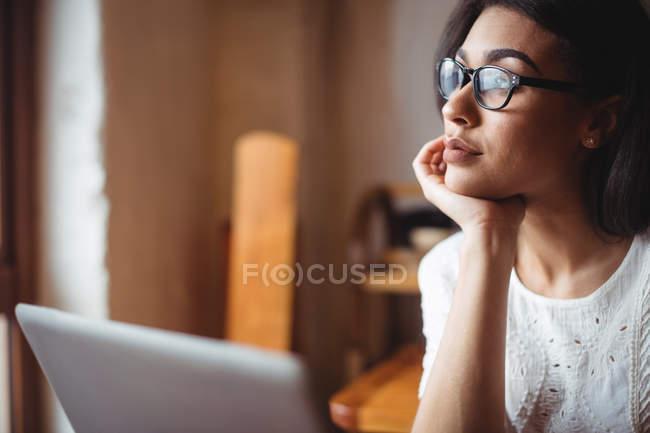 Задумчивая женщина сидит с ноутбуком в кафе — стоковое фото